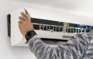 Man removing air conditioner.